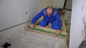 Hombre del carpintero que comprueba llano de nuevos pasos del tablero de la escalera con la nivelación de la herramienta almacen de metraje de vídeo