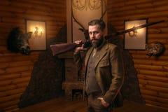 Hombre del cazador con el arma viejo contra pecho antiguo imagen de archivo libre de regalías