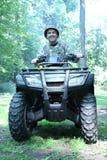 Hombre del cazador que conduce el atv de cuatro ruedas imágenes de archivo libres de regalías