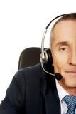 Hombre del centro de atención telefónica que se sienta en la oficina Foto de archivo