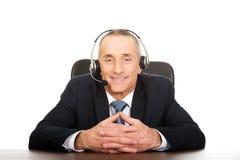 Hombre del centro de atención telefónica que se sienta en la oficina Foto de archivo libre de regalías