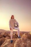 Hombre del cercador que se coloca encima de la roca que sostiene de cercado y una espada y mirada la máscara adelante seriamente Foto de archivo libre de regalías