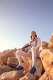 Hombre del cercador que se sienta encima de la roca que sostiene su de cercado y una espada en un fondo del cielo azul y mirada m Imagenes de archivo