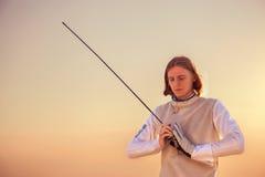 Hombre del cercador que sostiene su espada en ambas manos que miran abajo en fondo de la puesta del sol Imagen de archivo libre de regalías