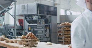 Hombre del cocinero del panadero del sector panadero con una barba que mira derecho a la sonrisa de la cámara grande mientras que almacen de metraje de vídeo