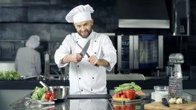 Hombre del cocinero que se ríe en el restaurante de la cocina Cocinero de sexo masculino sonriente que presenta con los cuchillos almacen de video