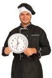 Hombre del cocinero que sostiene el reloj Imagenes de archivo