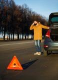 Hombre del conductor que examina los coches dañados del automóvil Imagen de archivo libre de regalías