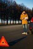 Hombre del conductor que examina los coches dañados del automóvil Foto de archivo libre de regalías