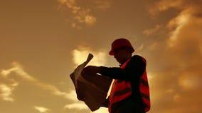 Hombre del constructor del trabajador de la silueta del trabajador con la camisa roja del casco y de los vaqueros cerca de una pa almacen de video