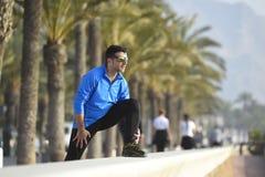 Hombre del corredor que estira en el bulevar de las palmeras de la playa con las gafas de sol en la sesión de formación de la sac Fotos de archivo libres de regalías