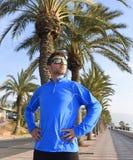 Hombre del corredor que presenta en el bulevar de las palmeras de la playa con las gafas de sol en la sesión de formación de la s Fotos de archivo libres de regalías