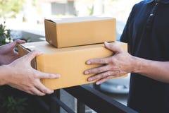 Hombre del correo de la entrega que da la caja del paquete al beneficiario, el aceptar joven del dueño del paquete de las cajas d foto de archivo libre de regalías