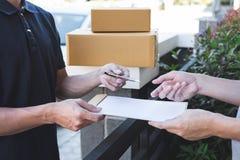 Hombre del correo de la entrega que da la caja del paquete al beneficiario, recibo de firma del hombre joven del paquete de la en imágenes de archivo libres de regalías