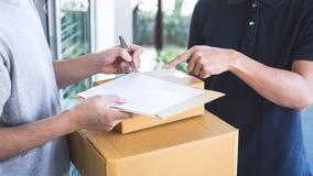 Hombre del correo de la entrega que da la caja del paquete al beneficiario, recibo de firma del hombre joven del paquete de la en fotos de archivo libres de regalías
