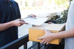 Hombre del correo de la entrega que da la caja del paquete a la forma del beneficiario y de la firma, recibo de firma del dueño j fotografía de archivo libre de regalías