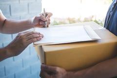 Hombre del correo de la entrega que da la caja del paquete a la forma del beneficiario y de la firma, recibo de firma del dueño j fotos de archivo