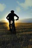 Hombre del deporte de la silueta que completa un ciclo el soporte en declive del campo a través del montar a caballo Imagen de archivo