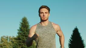 Hombre del deporte que corre en parque en fondo del cielo azul Funcionamiento masculino del corredor en parque almacen de metraje de vídeo
