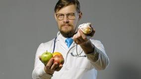 Hombre del doctor en la capa blanca en el fondo gris, concepto de la medicina almacen de video