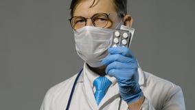 Hombre del doctor en la capa blanca en el fondo gris, concepto de la medicina almacen de metraje de vídeo
