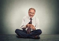 Hombre del ejecutivo 'senior' que se sienta en un piso usando música que escucha que manda un SMS del teléfono elegante Fotografía de archivo libre de regalías