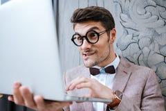 Hombre del empollón que sostiene el ordenador portátil y que hace la cara divertida Fotos de archivo libres de regalías