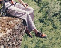 Hombre del escalador que se sienta en el borde del acantilado imagenes de archivo