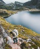 Hombre del escalador que sube en las montañas que sostienen cadenas Fotografía de archivo