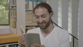 Hombre del estudiante del inconformista que se divierte que lee un libro interesante que expresa el asombro y el entusiasmo - almacen de metraje de vídeo