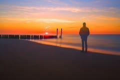 Hombre del fantasma que mira una puesta del sol en una playa imagenes de archivo