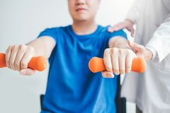 Hombre del fisioterapeuta que da ejercicio con el tratamiento de la pesa de gimnasia sobre el brazo y el hombro de la terapia fís imagen de archivo libre de regalías