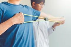 Hombre del fisioterapeuta que da el tratamiento del ejercicio de la banda de la resistencia sobre el brazo y el hombro de la tera imagen de archivo libre de regalías