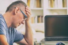 Hombre del Freelancer en el lugar de trabajo en la oficina que lleva a cabo su cabeza en las manos Imagen de archivo