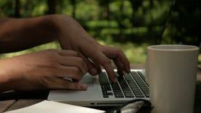 Hombre del Freelancer que trabaja en el ordenador portátil del ordenador en el fondo de la naturaleza del verde del parque almacen de video