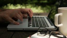 Hombre del Freelancer que trabaja en el ordenador portátil del ordenador en el fondo de la naturaleza del verde del parque almacen de metraje de vídeo