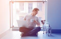 Hombre del Freelancer que usa el ordenador portátil y la taza de café foto de archivo