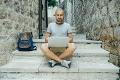 Hombre del Freelancer y un viajero que trabaja en un ordenador portátil en la calle imagenes de archivo