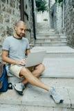 Hombre del Freelancer y un viajero que trabaja en un ordenador portátil en la calle imágenes de archivo libres de regalías