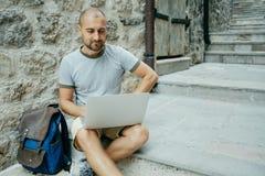 Hombre del Freelancer y un viajero que trabaja en un ordenador portátil en la calle fotografía de archivo