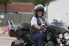 Hombre del funcionamiento del póker de la motocicleta con las banderas Fotografía de archivo