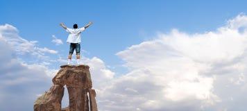 Hombre del ganador que se coloca en el top de la montaña imagen de archivo
