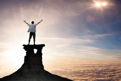 Hombre del ganador que se coloca en el top de la montaña foto de archivo