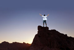 Hombre del ganador que se coloca en el top de la montaña imagenes de archivo