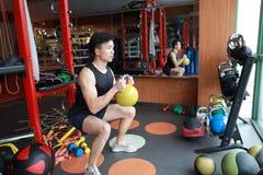 Hombre del gimnasio en gimnasio que se resuelve usando los kettlebells interiores Hermoso, prensa fotografía de archivo libre de regalías