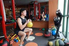 Hombre del gimnasio en gimnasio que se resuelve usando los kettlebells interiores Hermoso, prensa imagen de archivo libre de regalías