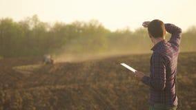 Hombre del granjero leído o análisis un informe en tableta en un campo de la agricultura con tono del vintage en una luz del sol  almacen de metraje de vídeo
