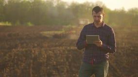Hombre del granjero leído o análisis un informe en tableta en un campo de la agricultura con tono del vintage en una luz del sol  metrajes