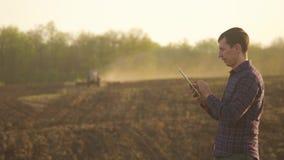 Hombre del granjero leído o análisis un informe en tableta en un campo de la agricultura con tono del vintage en una luz del sol  almacen de video