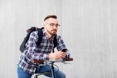 Hombre del inconformista con la bici y la mochila fijas del engranaje imagenes de archivo